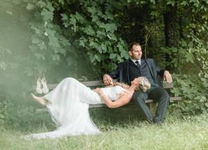 Brautpaar im Wald auf Bank sitzend