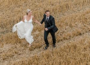 Brautpaar in Feld rennend