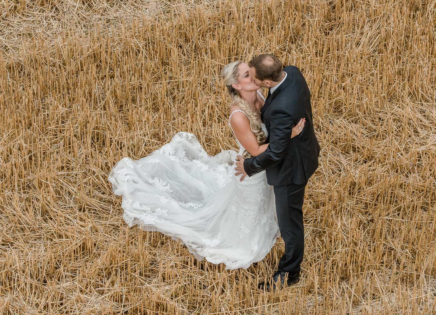 Brautpaar im Feld küssend