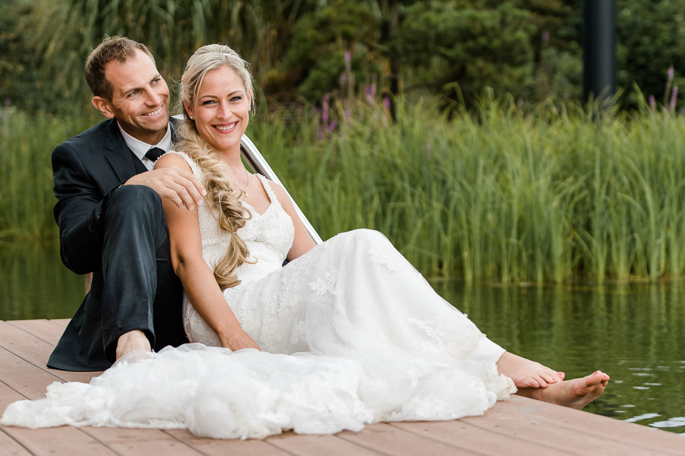 Brautpaar am Teich sitzend auf Steeg