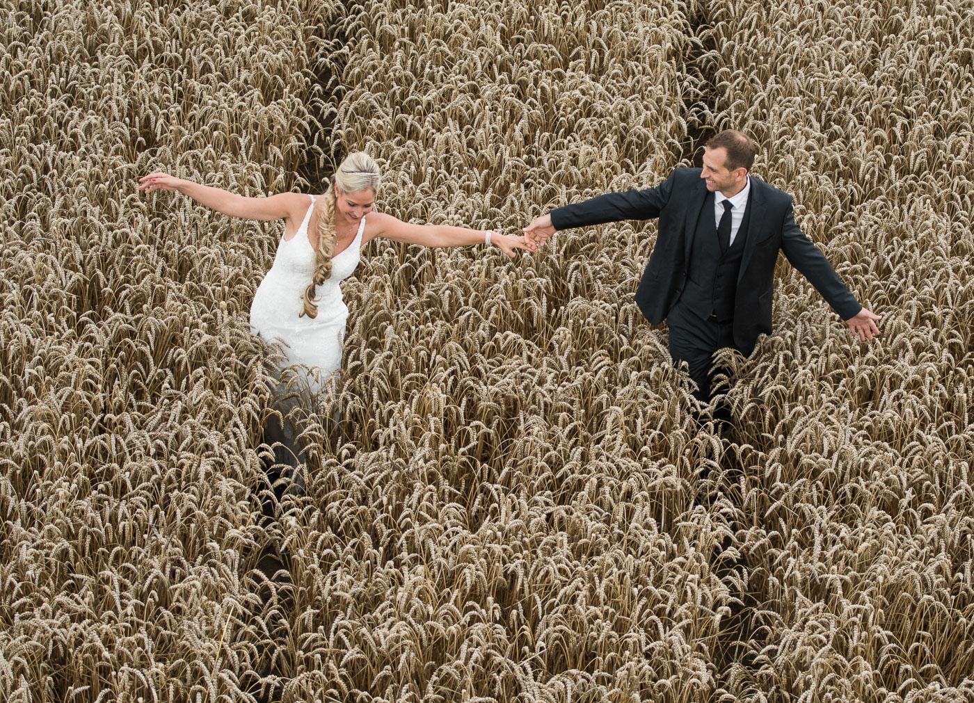 Brautpaar im Kornfeld laufend